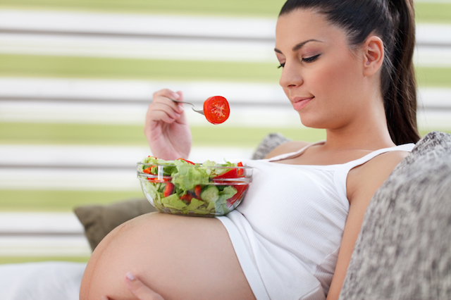 Beautiful healthy young pregnant woman eating vegetable salad